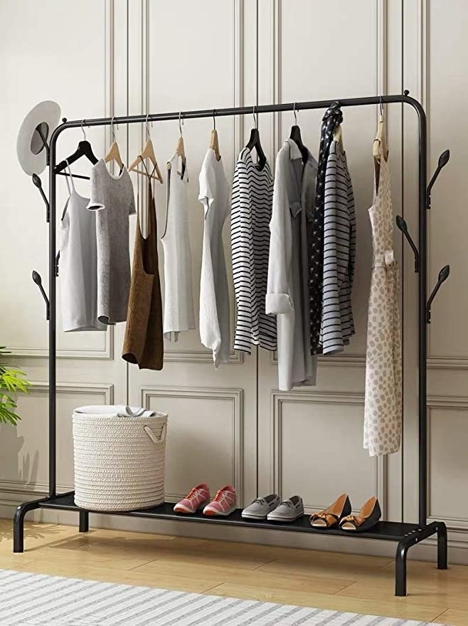 The rack used to hang clothes and store a hat, laundry basket, and shoes