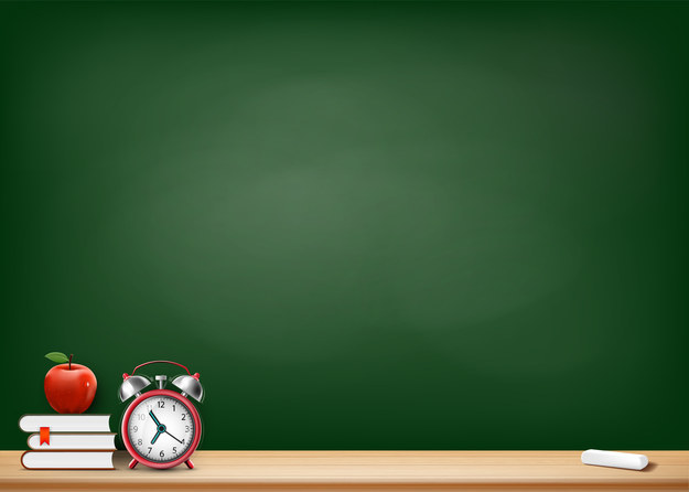 a blackboard in a classroom and a table that contains some books, an alarm clock, a chalk, and an apple. the text on the board says check off all the things your teachers have said or done
