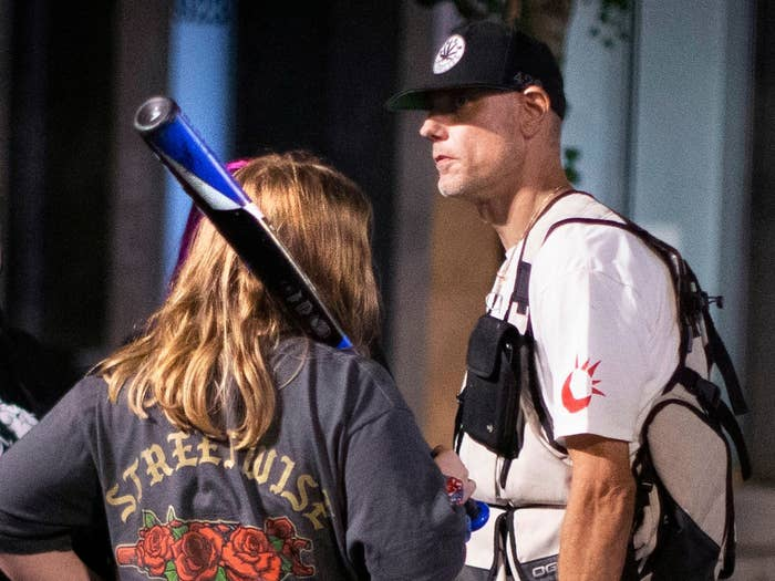 A tall man wearing a baseball cap stands next to a person with long hair holding a baseball bat whose back is to the camera.