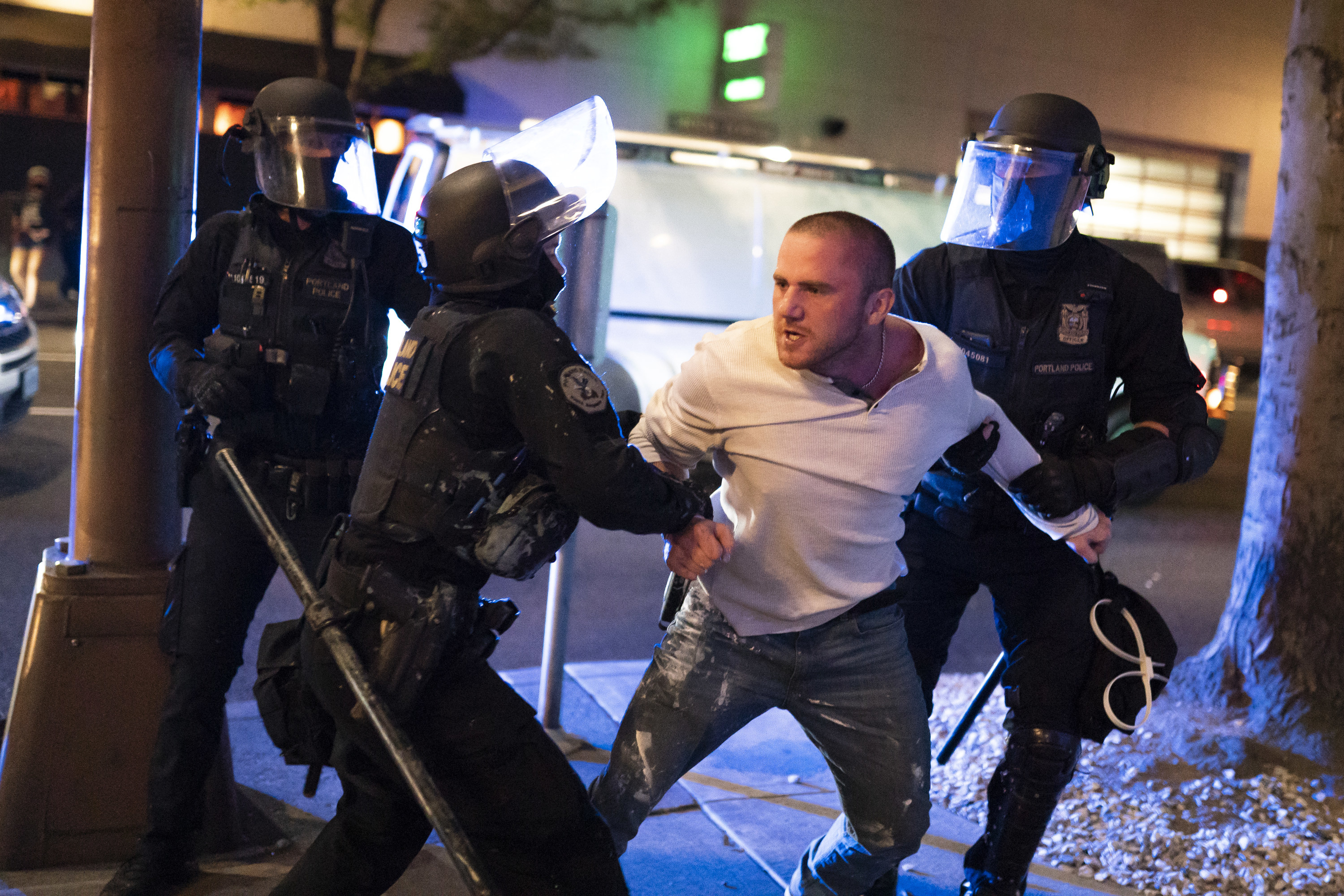 A man looks shocked as he is restrained by three officers wearing riot gear.