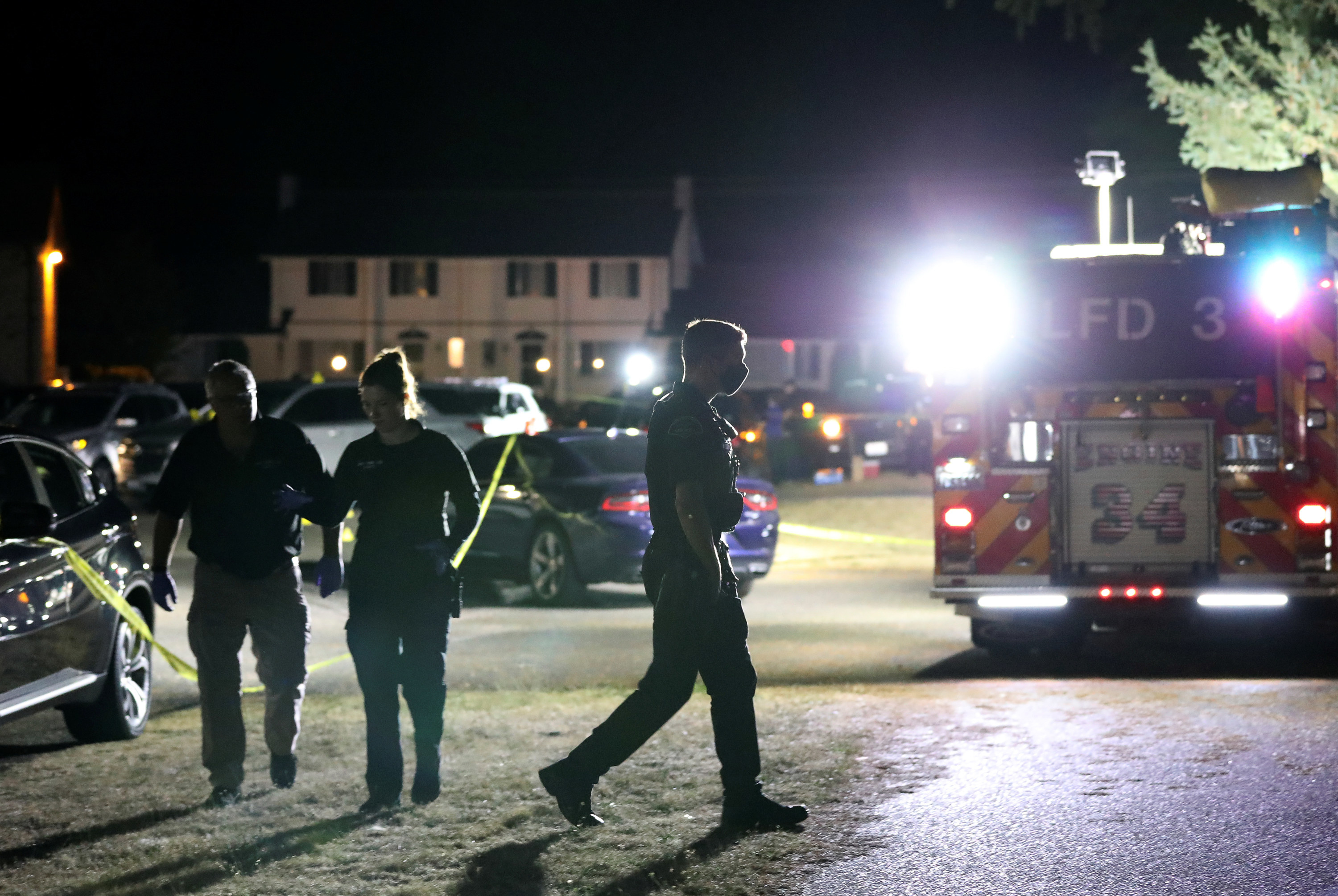 Three people walk among cars as a fire truck shines its lights at the camera.