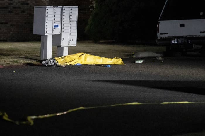 A tarpaulin covers a body as it lies next to a mailbox on a street at nighttime.