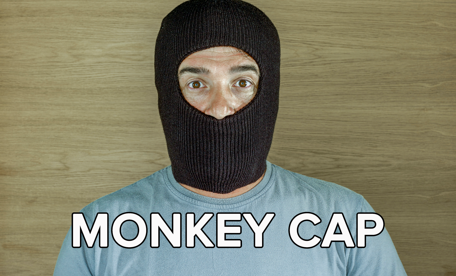 A person wearing a balaclava stares at the camera