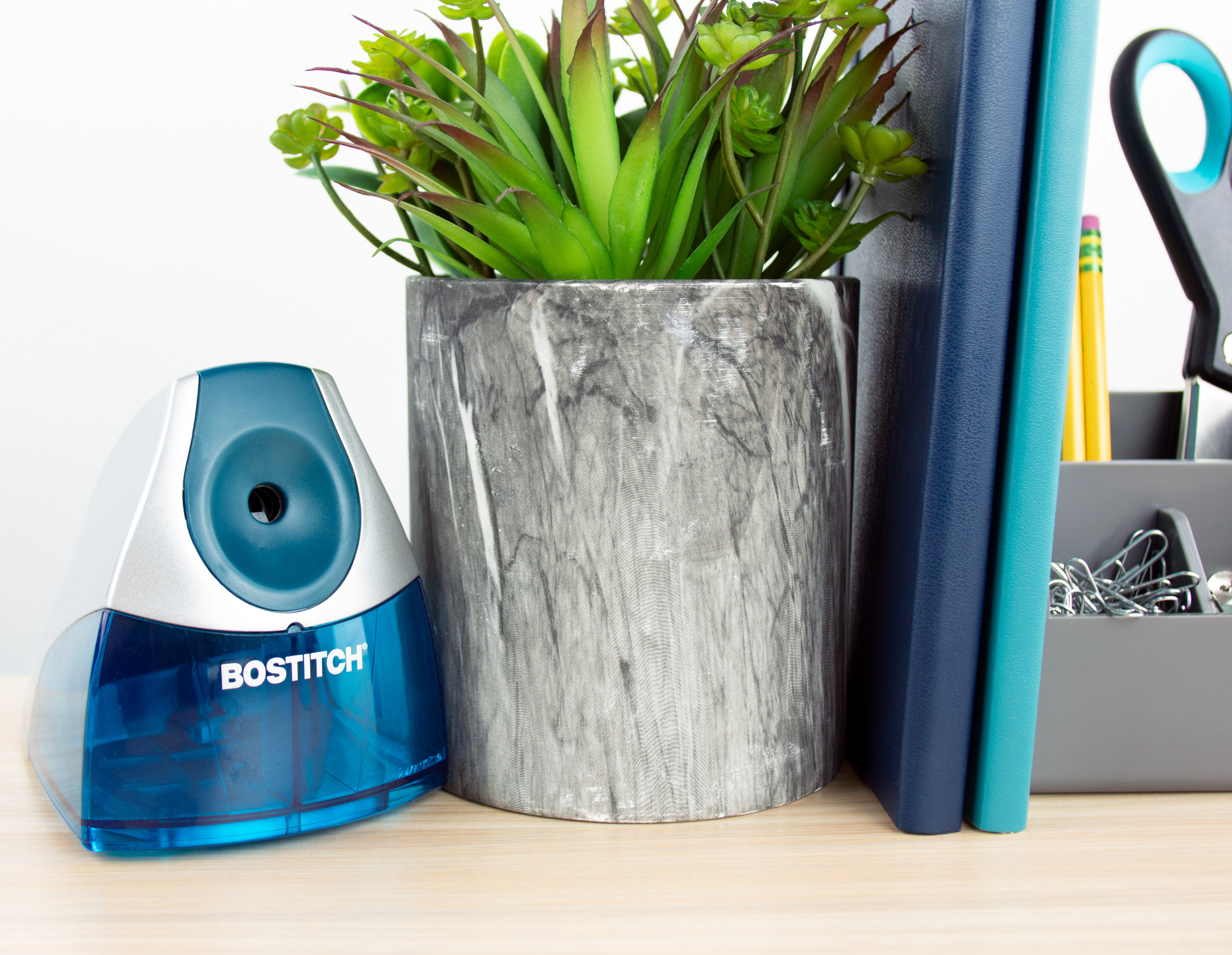 blue Bostitch electric pencil sharpener sitting on a desk next to a plant