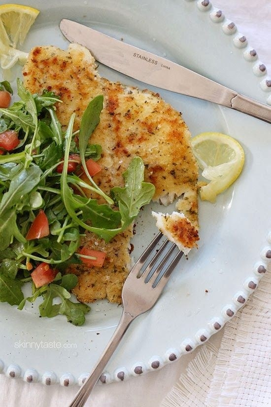 A fork cutting a piece of flaky, breaded flounder topped with arugula and tomato salad.