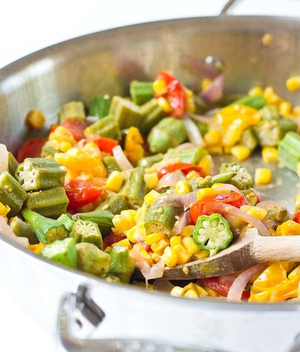A skillet with corn, onion, tomato, and okra.