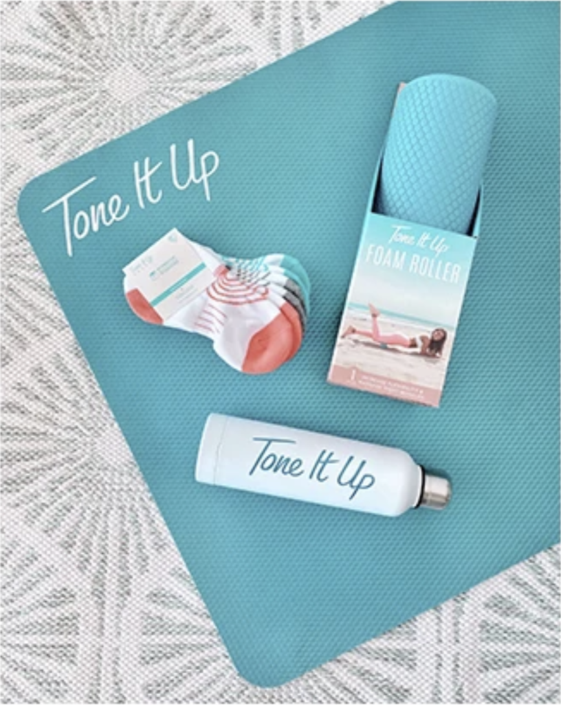 A teal yoga mat with socks, a foam roller, and a water bottle on top of it