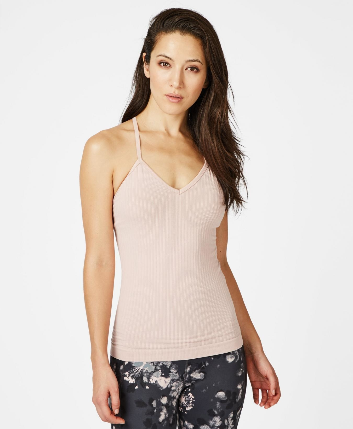 Model wearing the ribbed v-neck spaghetti strap tank in light pink