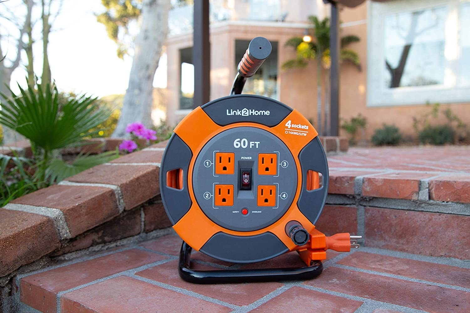 the orange and grey extension cord winder with four outlets in the middle of it
