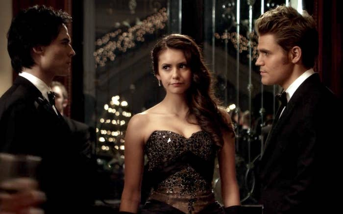 Elena walking into the Originals's ball with Damon and Stefan