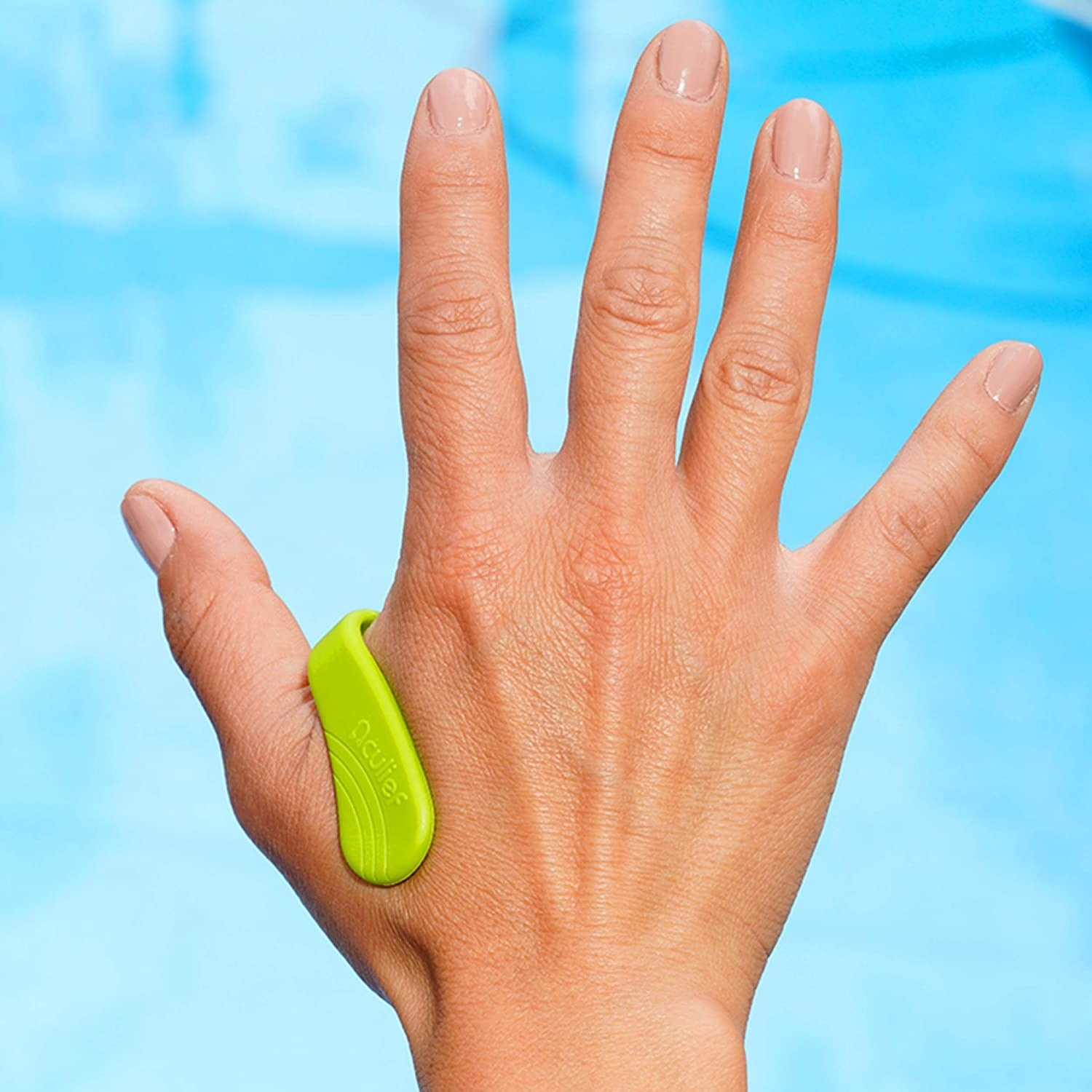 A person holds out their hand while wearing the acupressure tool between their thumb and index finger