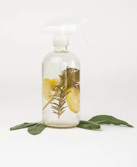 Honeydipped Essentials' Sage + Citrus Multipurpose Cleaner spray bottle with lemon slices and sage leafs inside