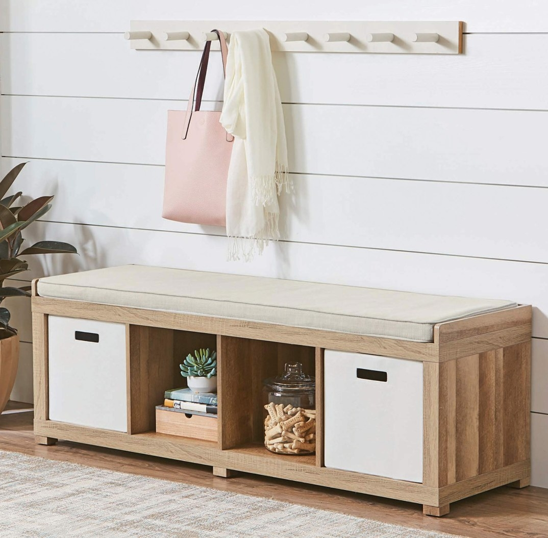 The wooden bench organizer with a cream seat holding a plant and books