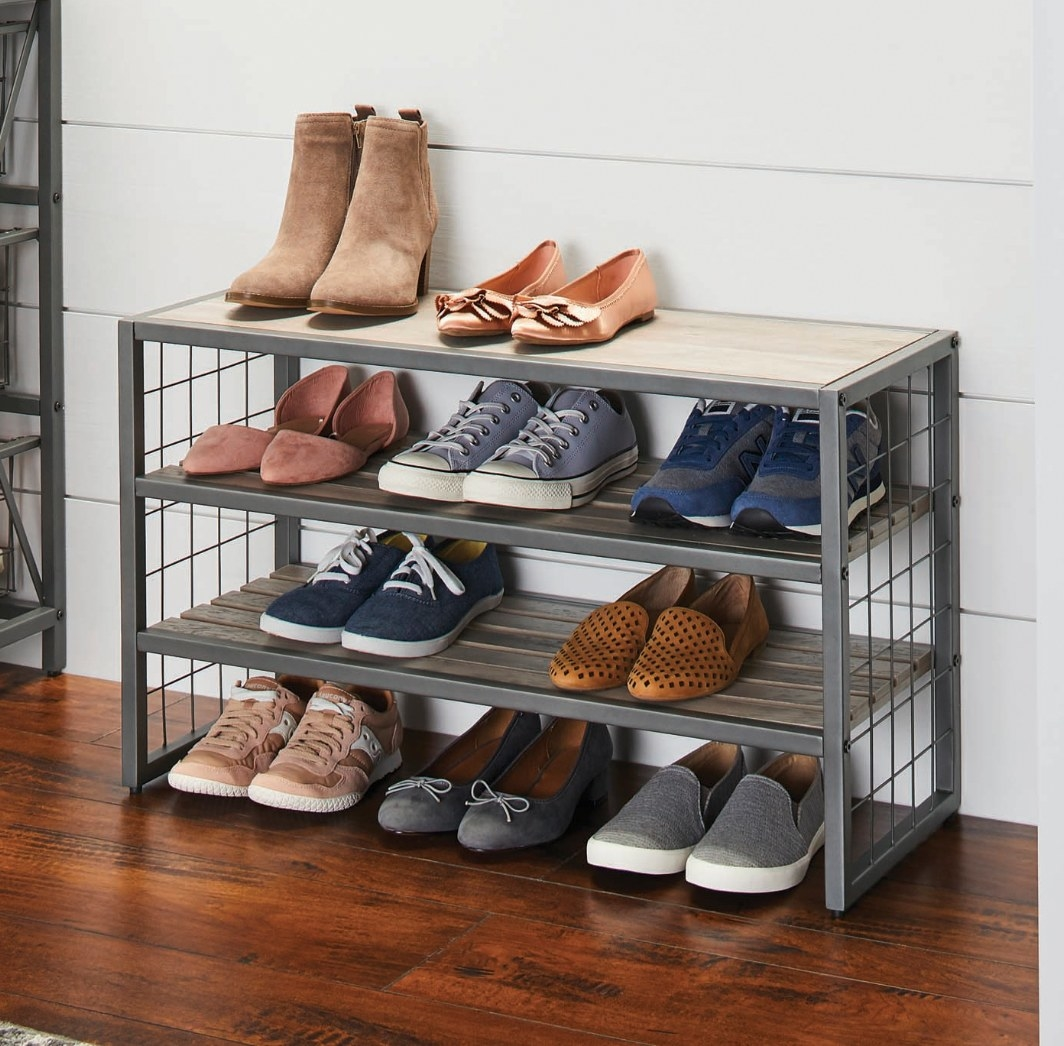 The gray metal and wood shoe rack being used to hold sneakers and flats