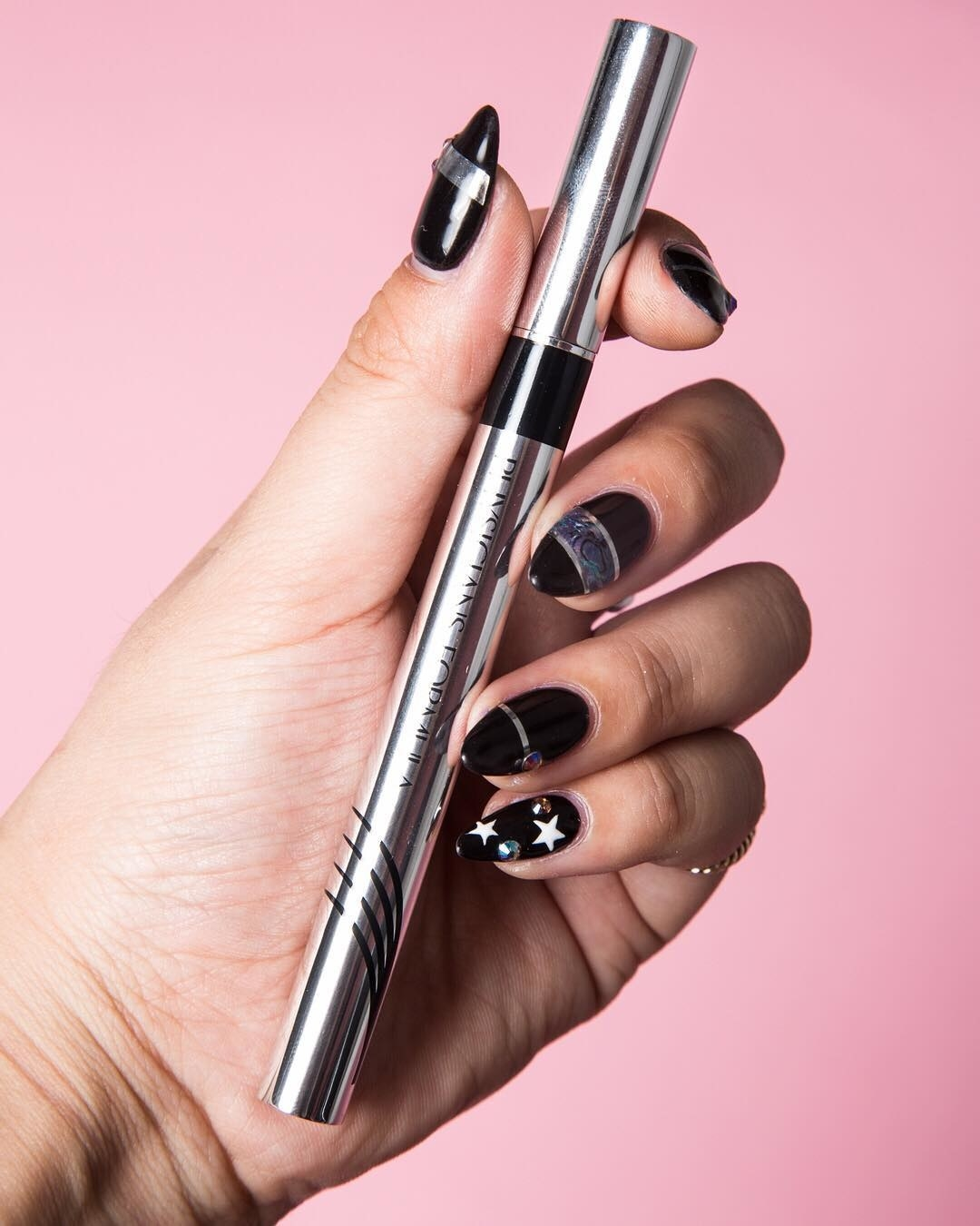 A person holds the eyeliner in their hand