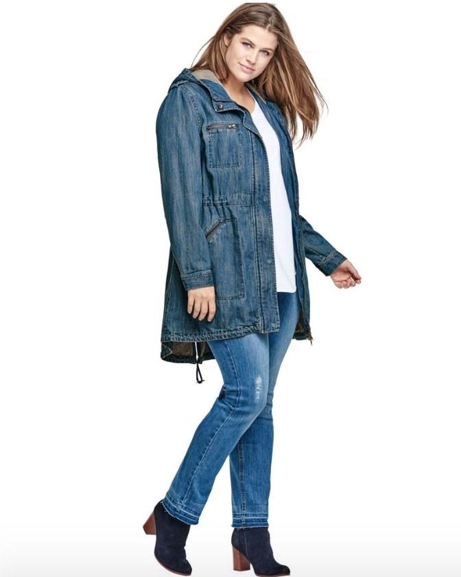 Model wearing mid length denim jacket with hood
