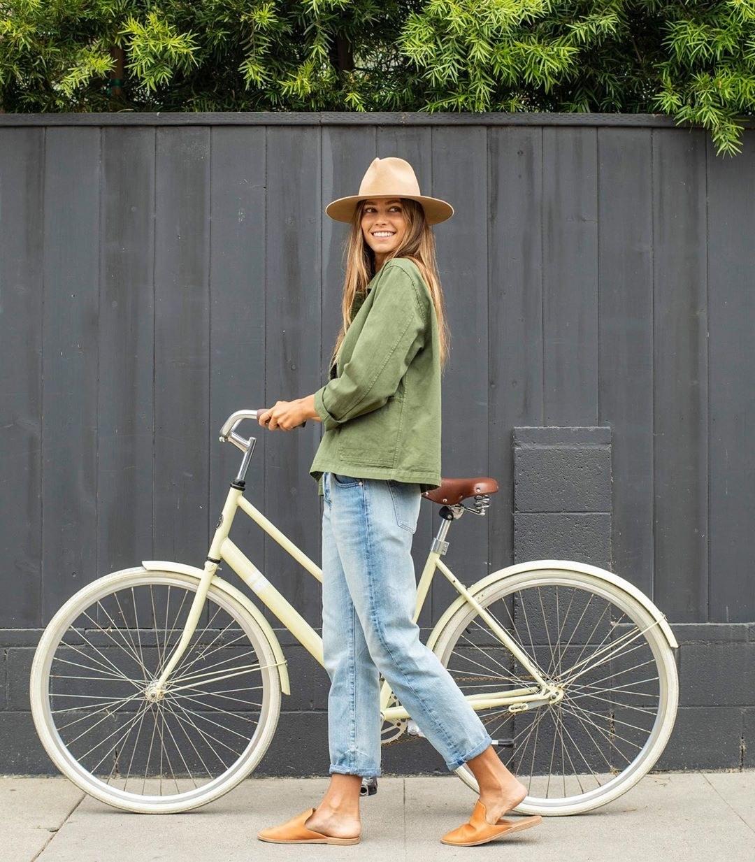 A model wears a green cotton denim jacket with jeans, as she walks her bike on the sidewalk