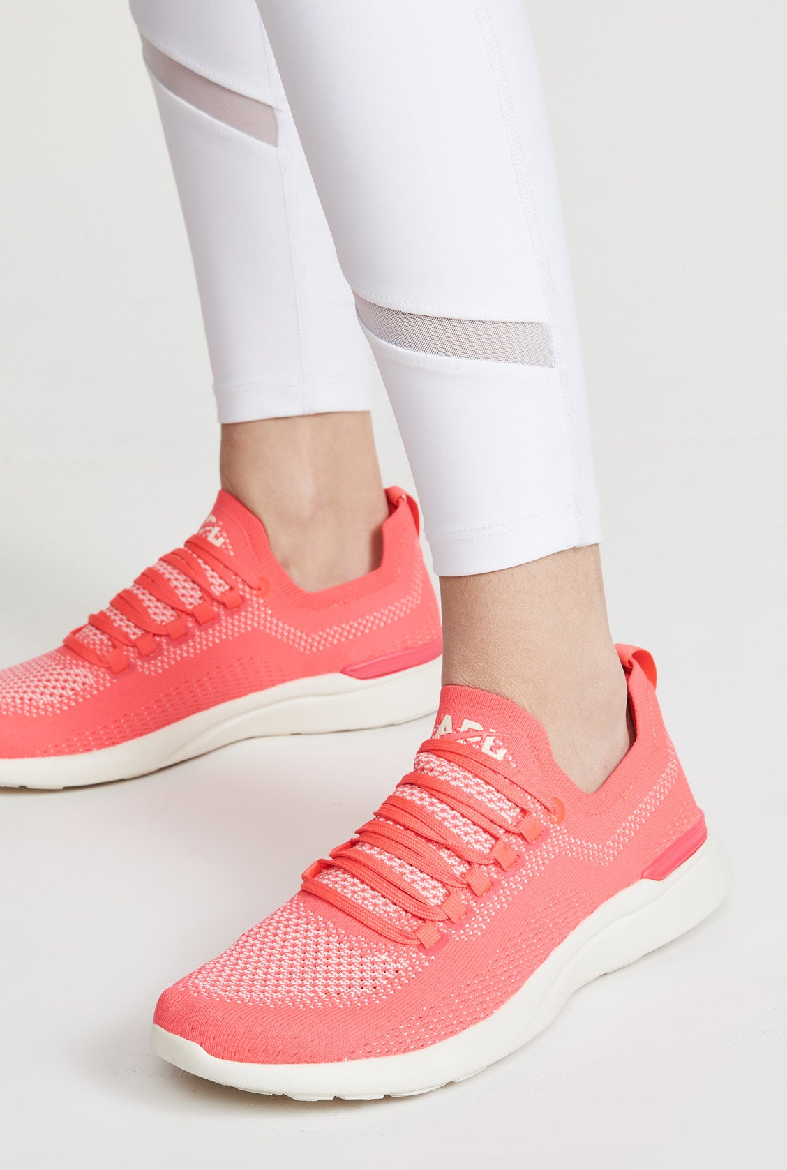 The sneakers with a bright pink and white knit body and white sole
