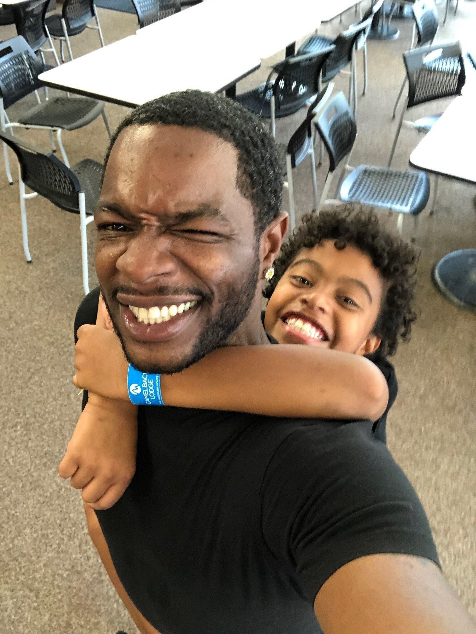 Kyle holds onto his dad's back as they pose for a selfie
