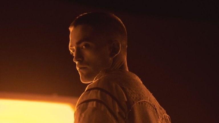 Robert Pattinson in space garb looking over his shoulder in an eerily glowing room