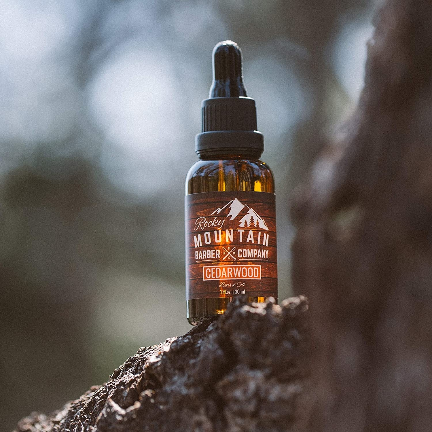 A bottle of the beard oil on a mountain rock
