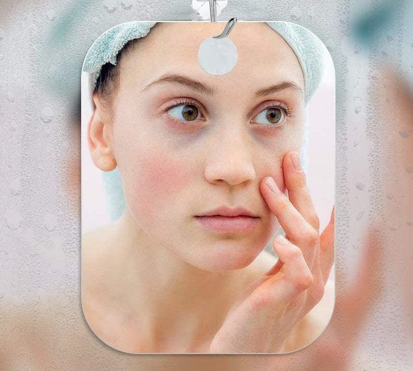 A person inspects their face in the fogless mirror that hangs on a fogged-up mirror in the bathroom