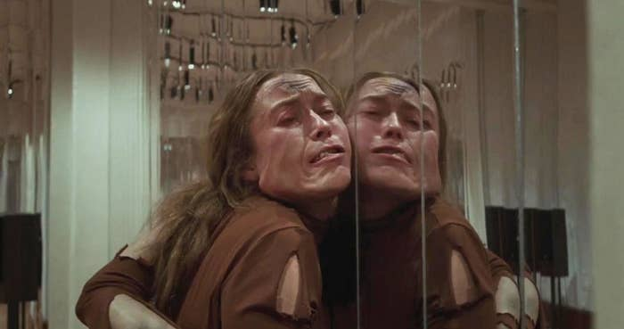 A disfigured dancer with her face pressed against a ballet mirror