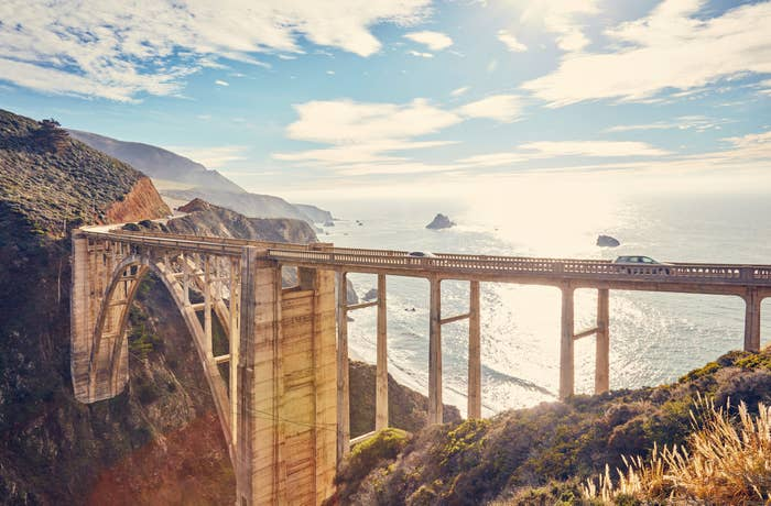 Bixby Creek Bridge at sunset with rocky cliffs and a view out across the ocean