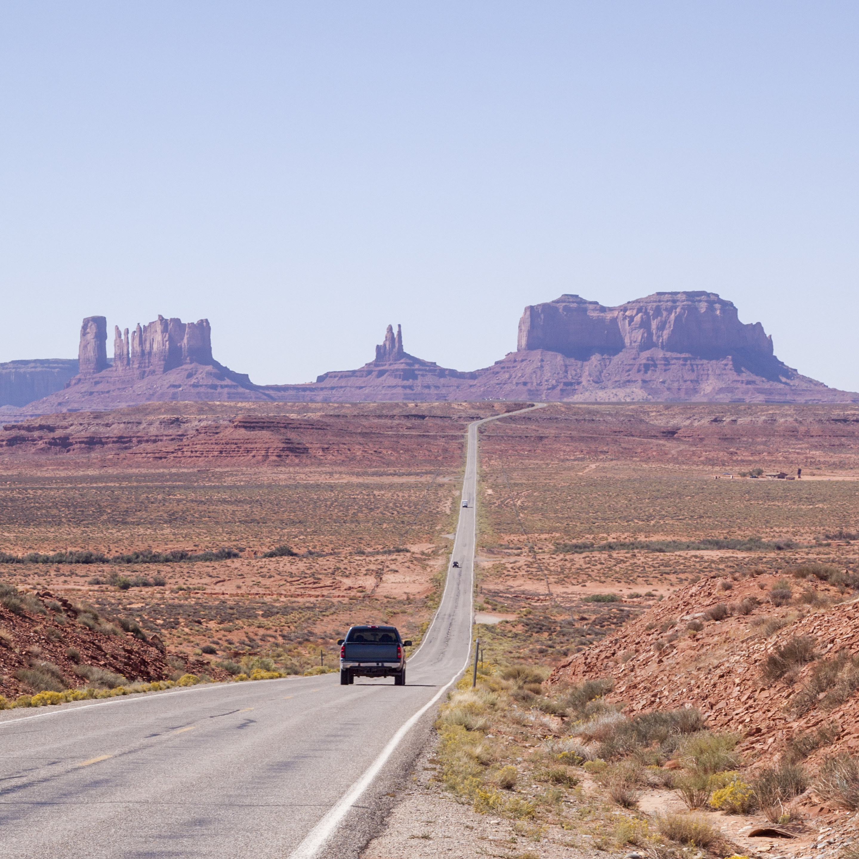 car driving down a long stretch of road towards Monument Valley