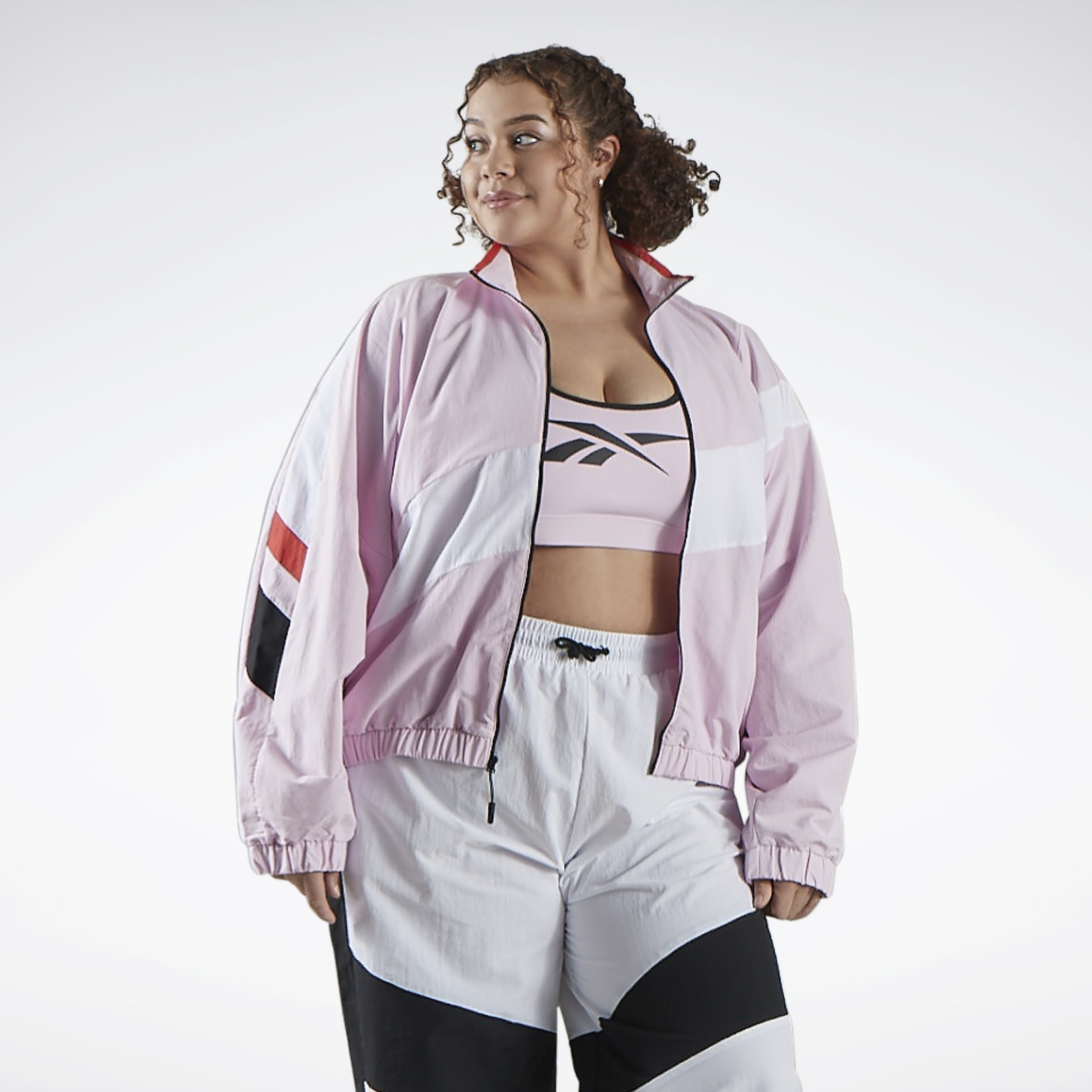 Model wearing the zip-front jacket in light pink with a white panel through the middle and black and red stripes on the side