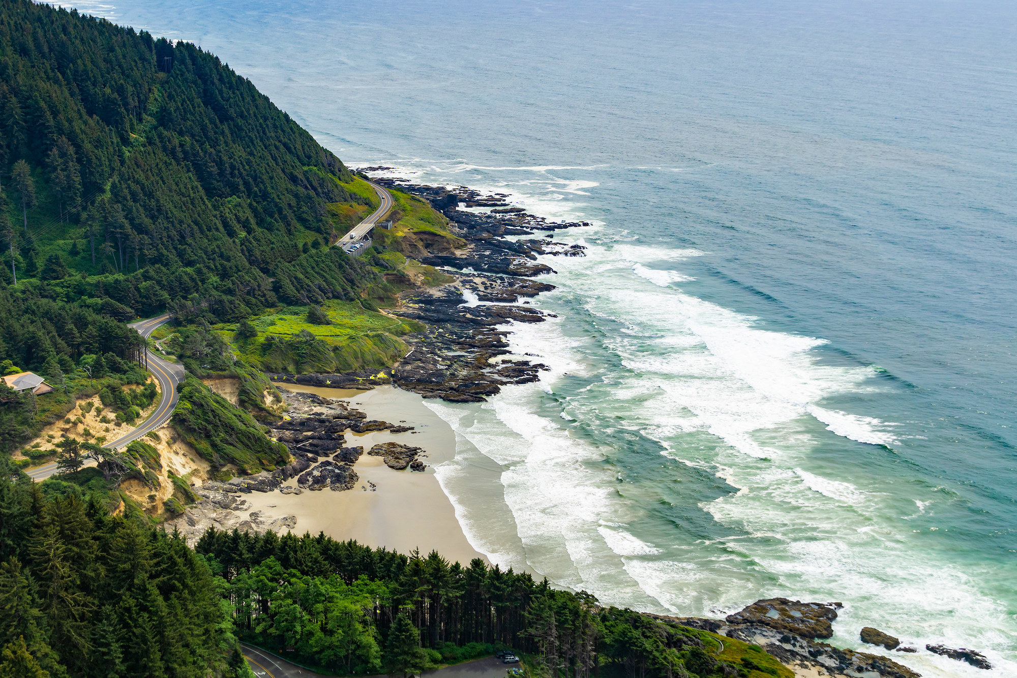 aerial view of road traveling along rocky coast with waves crashing on the shore
