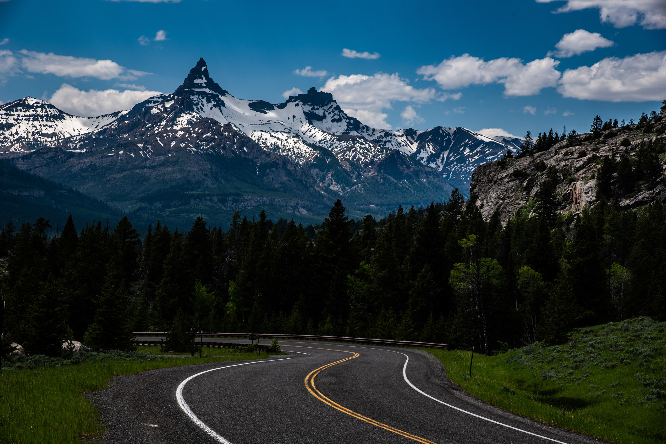 The Beartooth highway winding around a bend with snow capped mountains in the distance