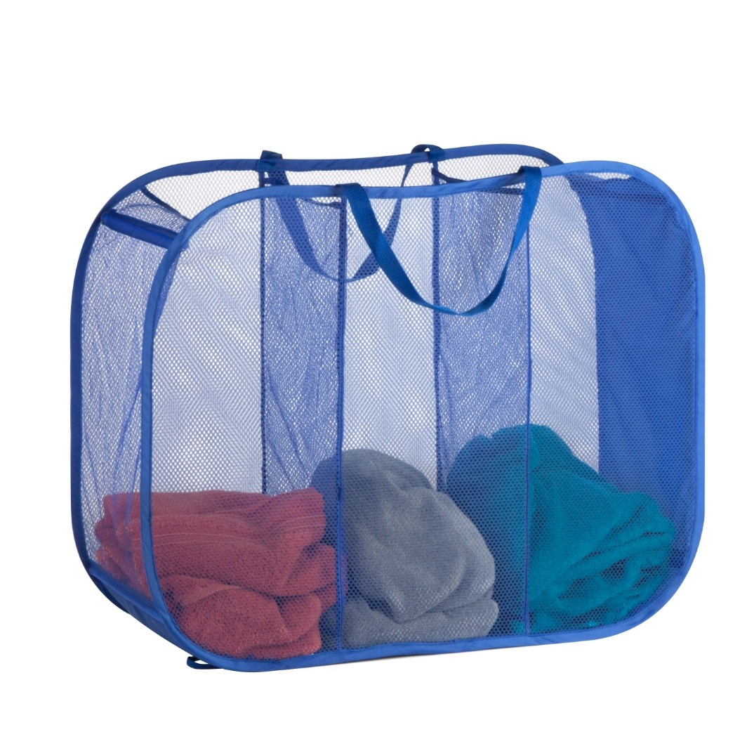 The blue laundry basket holding different colored towels in each compartment
