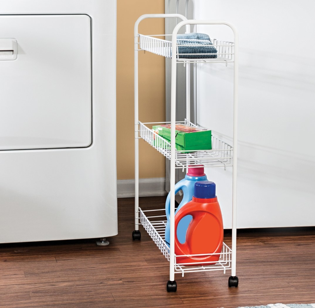 The white rolling cart being used in the laundry room to hold detergent and rags