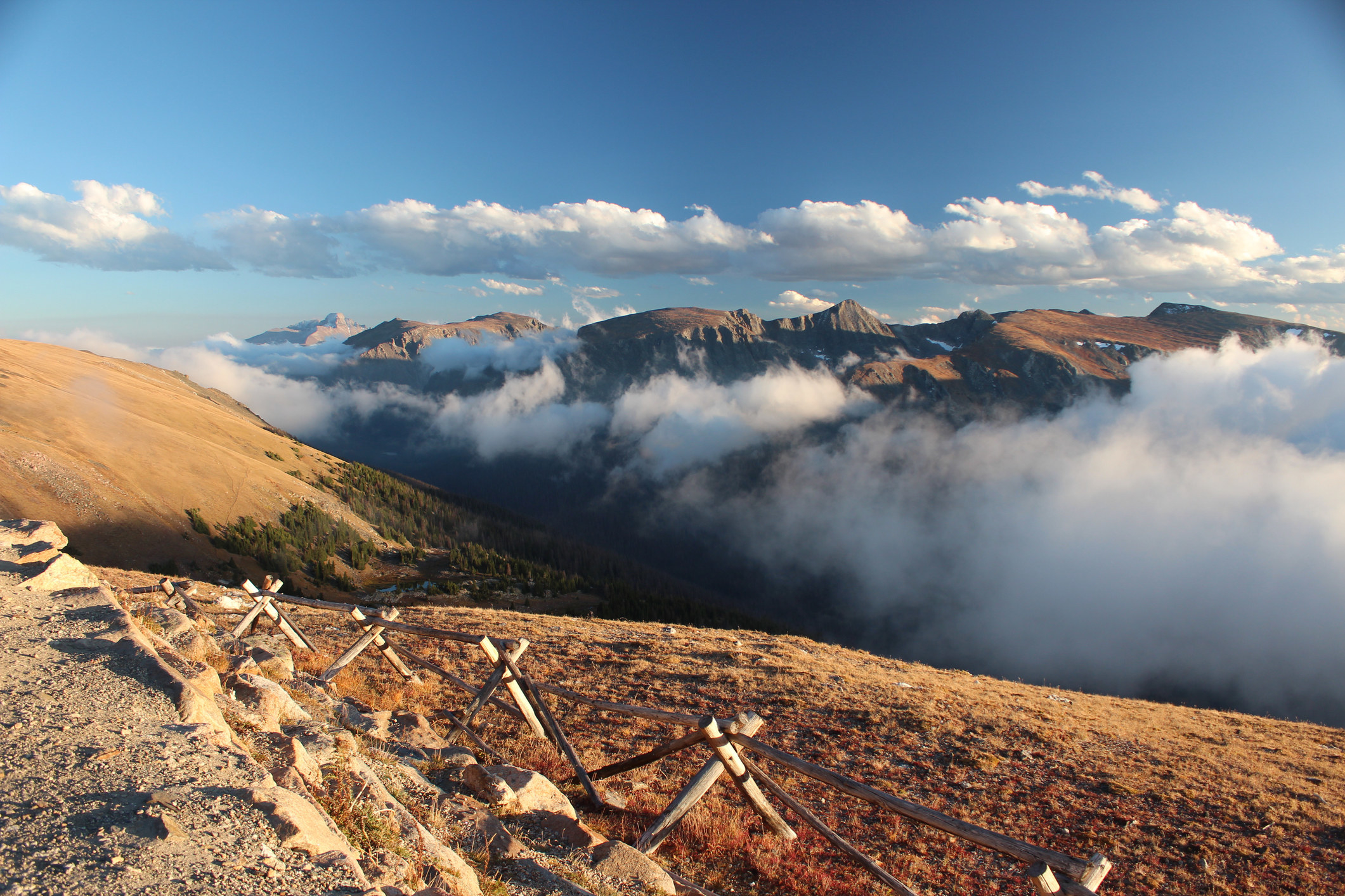 mountains poke above the clouds along Trail Ridge Road in Rocky Mountain National Park during the fall