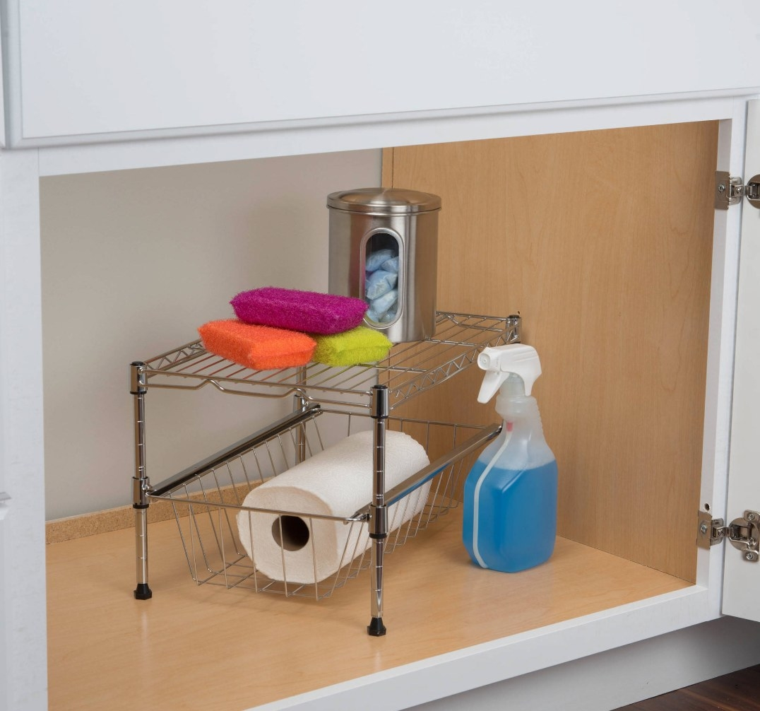 The cabinet organizer holding a paper towel roll and sponges