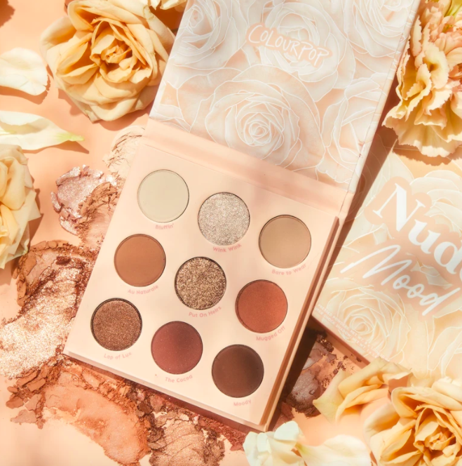 ColourPop's Nude Mood shadow palette in front of a pink backdrop of white roses