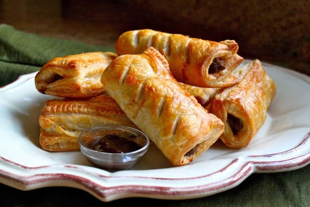 A plate of stacked sausage rolls with flaky, brown pastry dough and a peek of ground sausage poking through