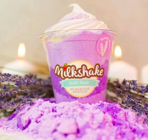 Nectar Bath Treats' purple Lavender Blossom Milkshake Bath Soak in a milkshake container next to white candles