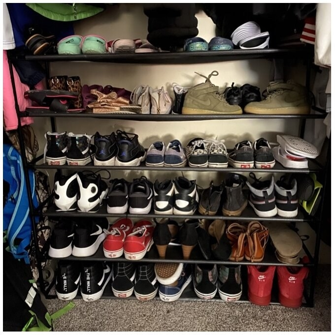 A reviewer photo of the tiered shoe rack holding various pairs of shoes neatly