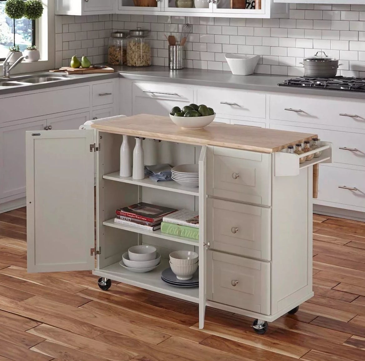 The kitchen cart on casters, three drawers, a built-in spice rack, an attached paper towel holder, and a cabinet with three shelves