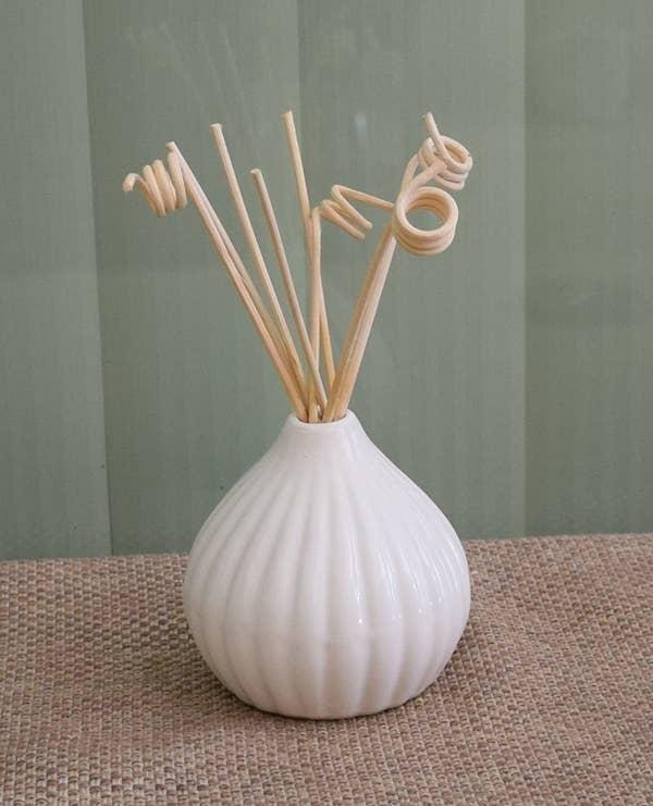 A white ceramic pot with reeds sticks