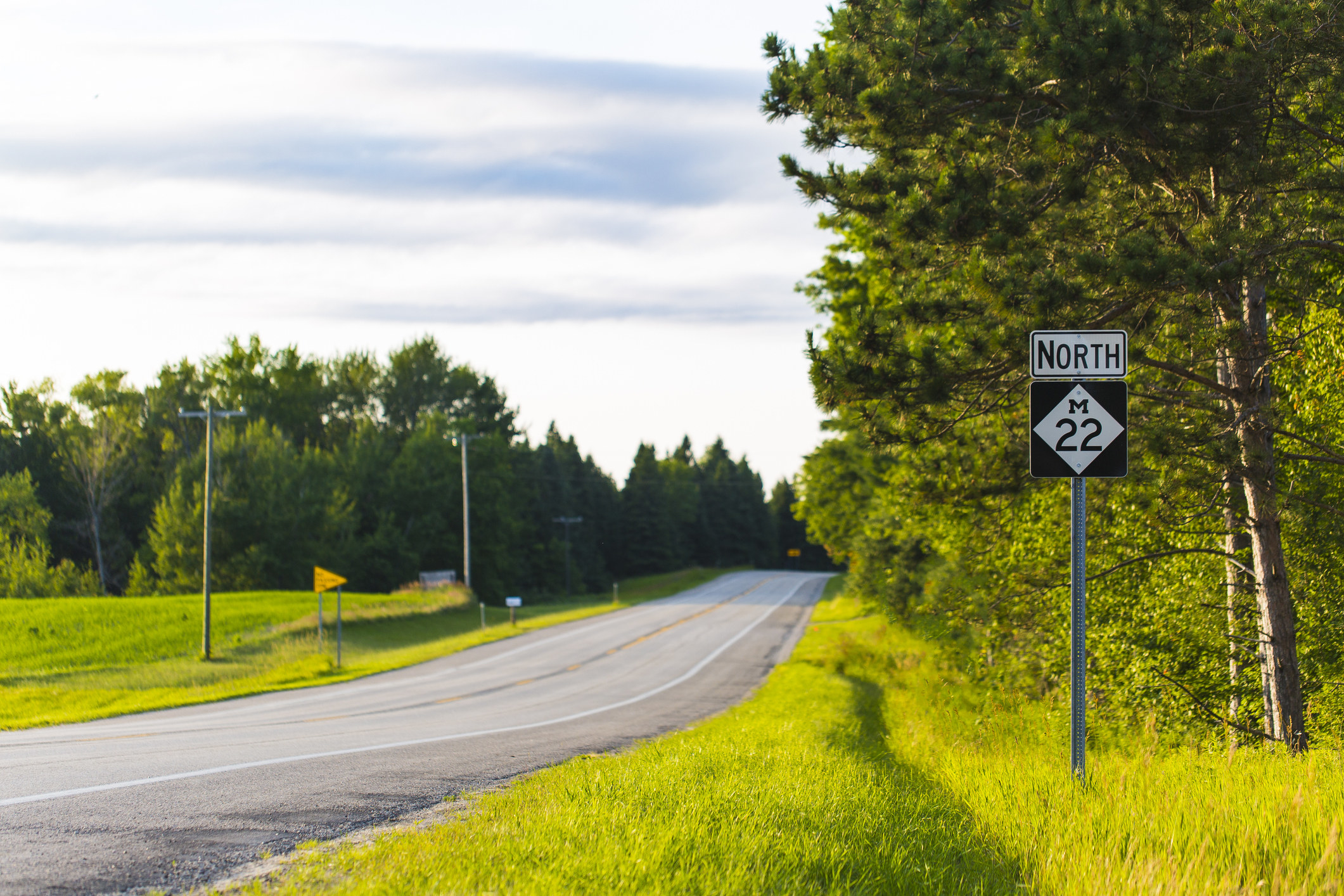 """long stretch of road surrounded by grass and trees with a sign reading """"north M22"""""""
