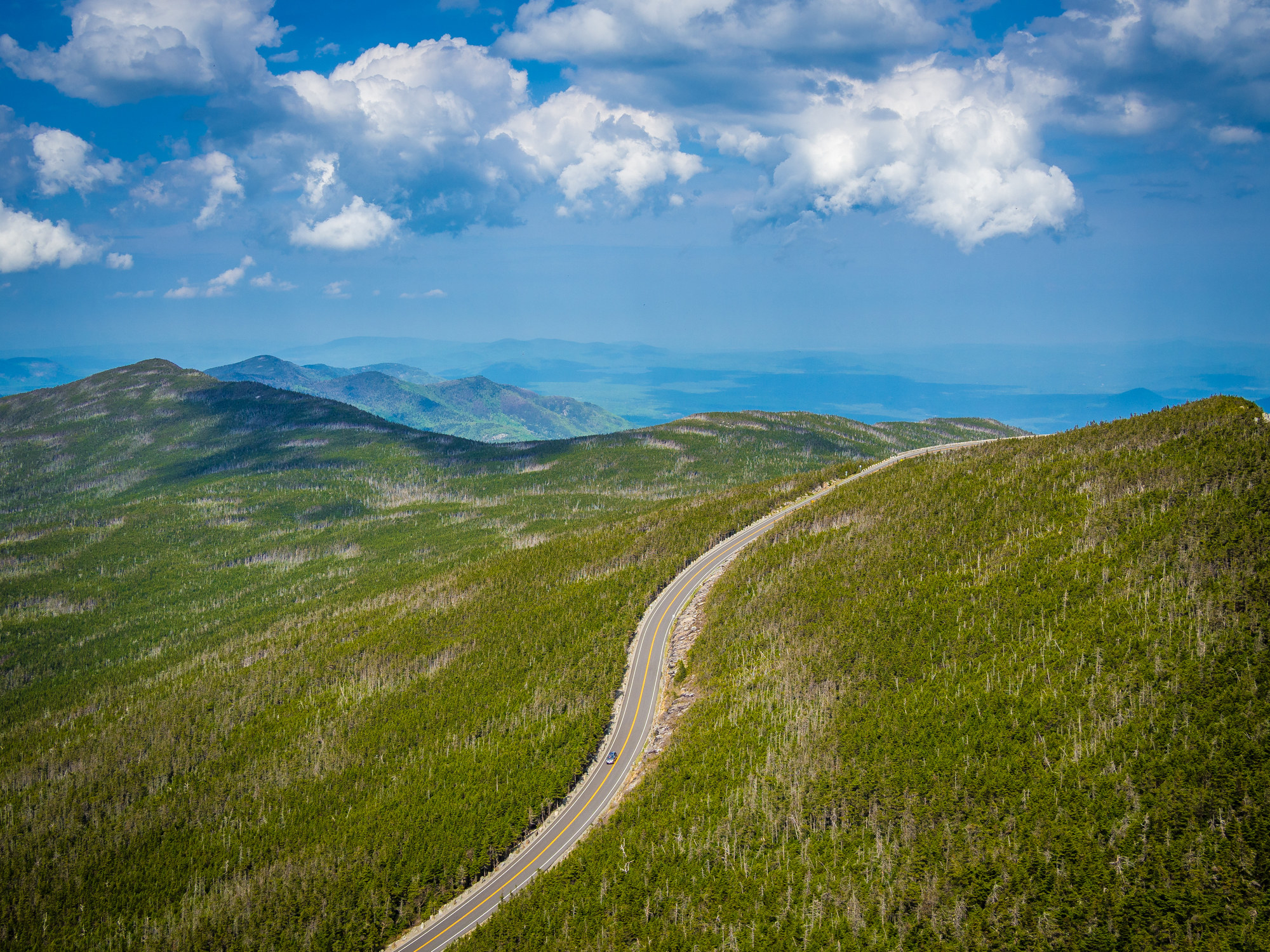 aerial view of road winding through Whiteface mountain, surrounded by greenery in Adirondack, NY, USA