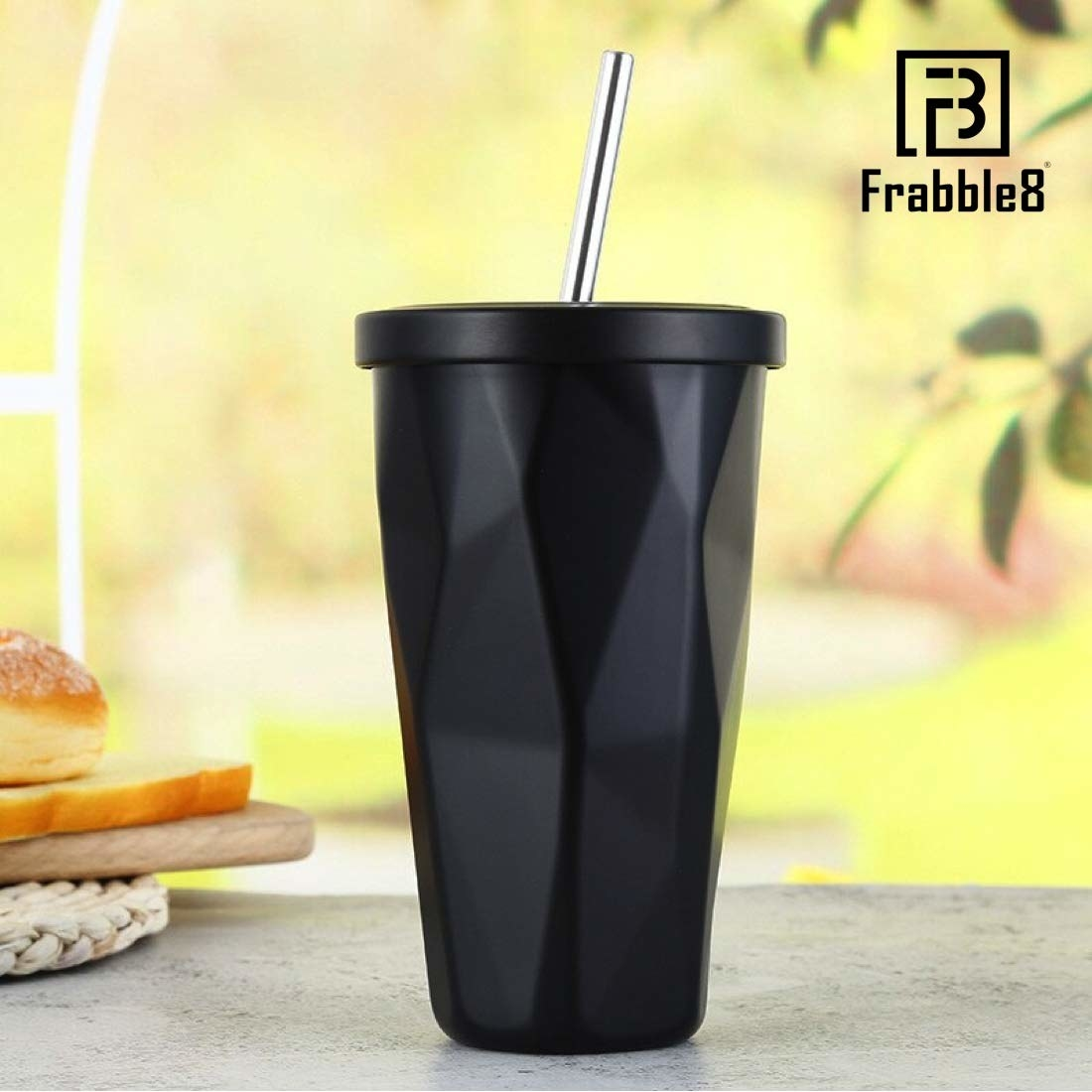 A black tumbler with a straw on a table