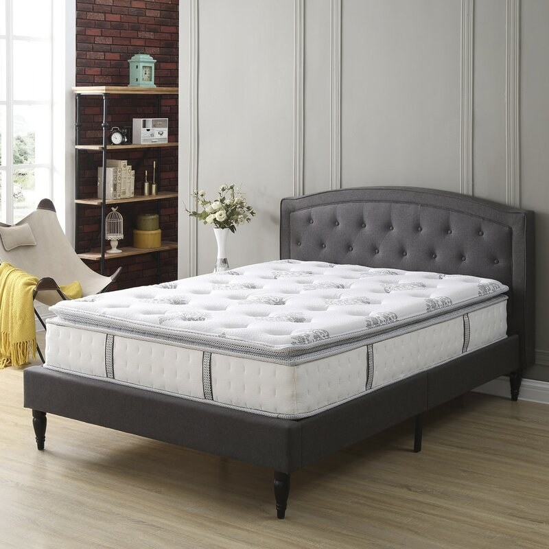 A white pillow top mattress with gray trim and a floral pattern on top