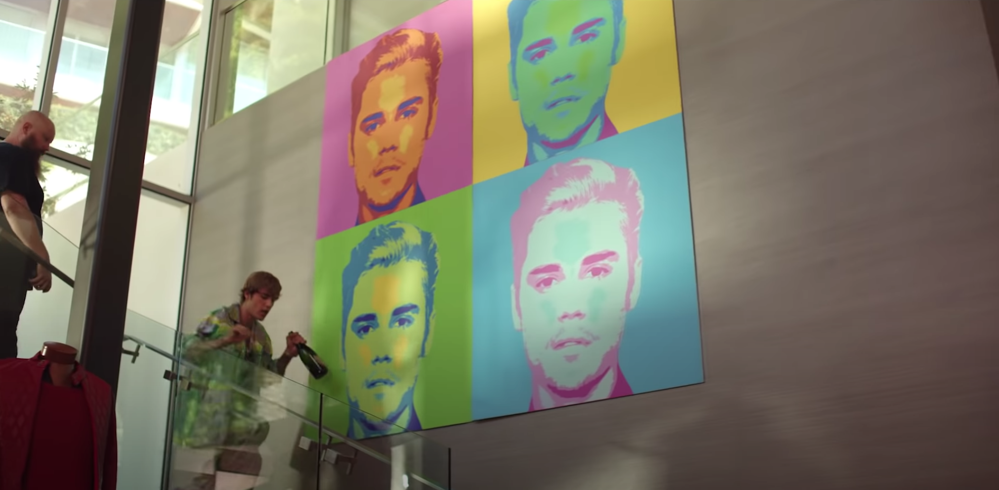 Justin walks by a colorful Andy Warhol-style pop art portraits of himself