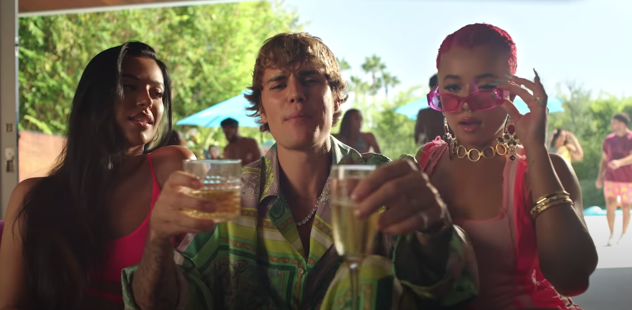 Justin sits among guests with drinks in his hands