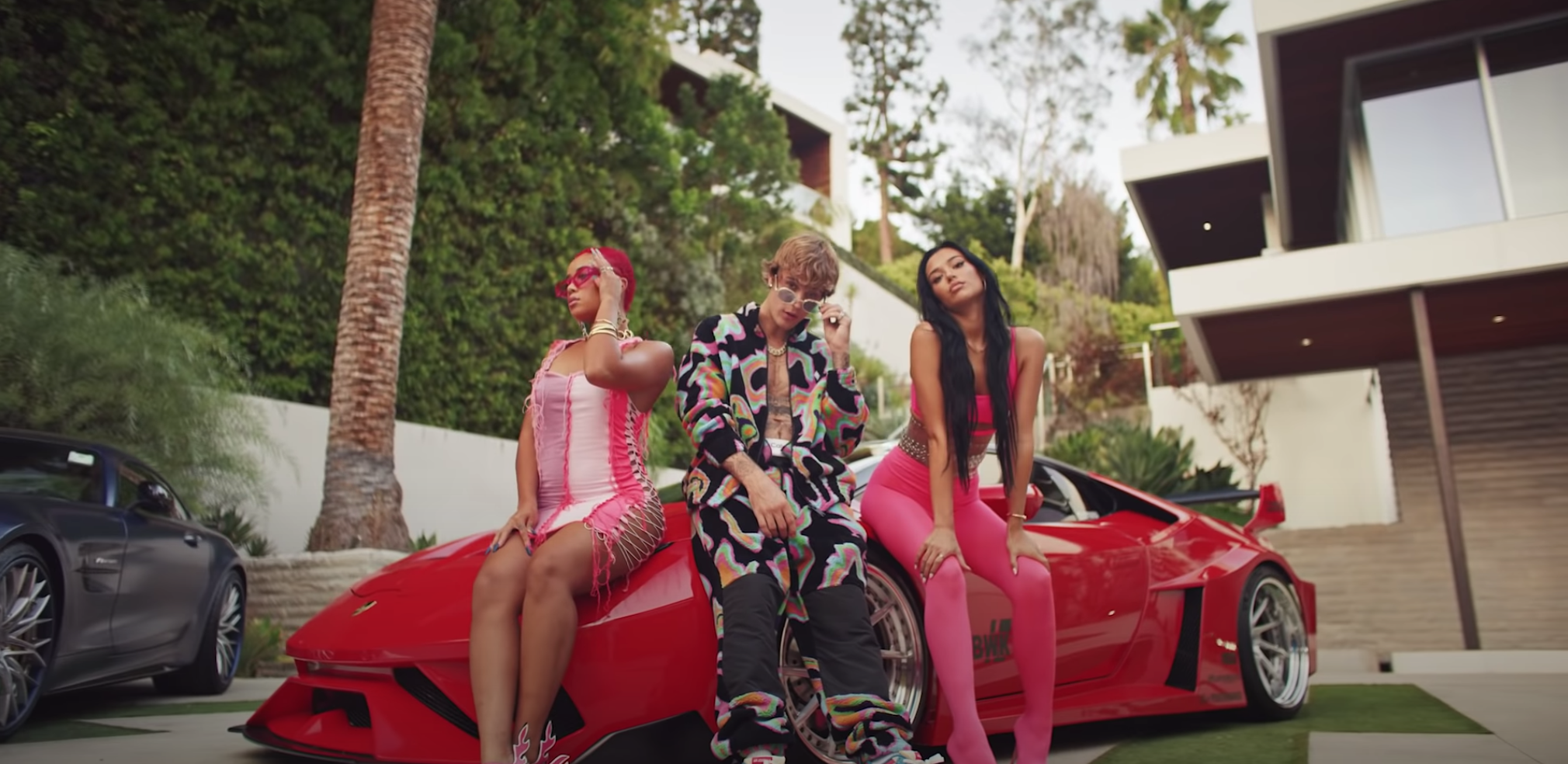 Justin poses with guests in front of expensive cars outside