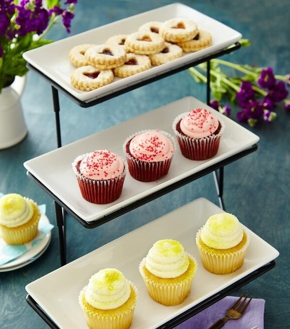 The three-tier, white serving tray on black metal frame with cupcakes on each tray